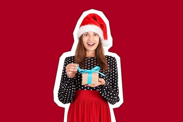 Lächelnde und glückliche frau, die eingewickelte geschenkbox anbietet. trendige farbe im stil einer zeitschriftencollage. ferien