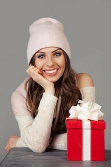 Lächelnde und glückliche, schöne junge frau in der winterkleidung mit einer roten weihnachtsgeschenkbox auf einer grauen wand. das mädchen genießt weihnachtseinkäufe, trifft das neue jahr. einkaufsverkaufskonzept.