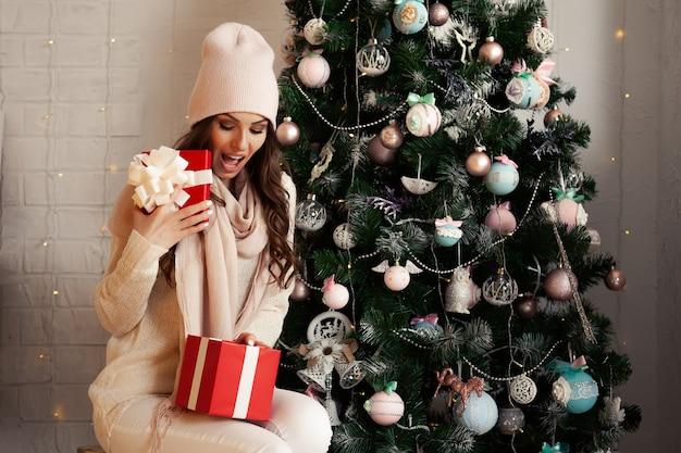 Lächelnde und glückliche, schöne junge frau in der winterkleidung mit einer roten weihnachtsgeschenkbox über einem geschmückten weihnachtsbaum.