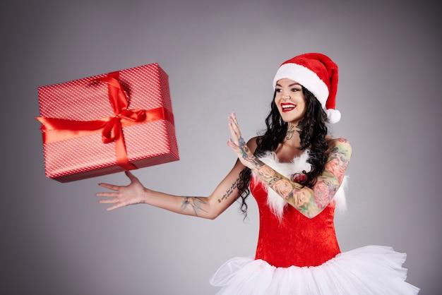 Lächelnde und schöne frau, die großes, rotes weihnachtsgeschenk fängt
