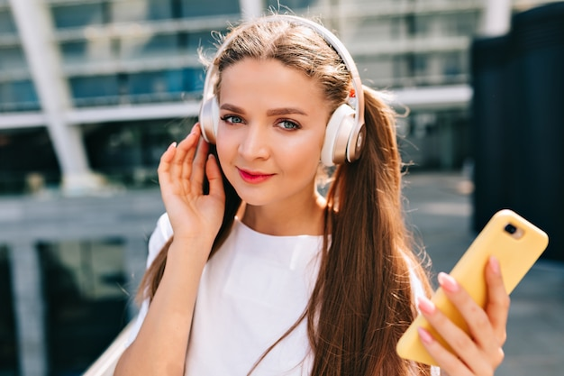 Lächelnde und tanzende junge frau, die ein smartphone hält und musik in kopfhörern hört