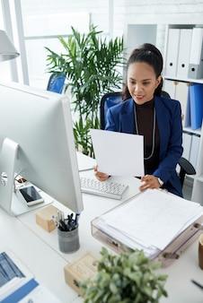 Lächelnde unternehmerin, die daten im verkaufsbericht analysiert, wenn sie am schreibtisch arbeitet