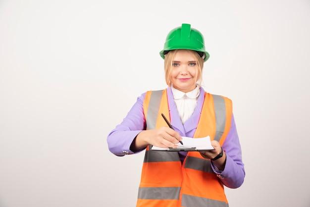 Lächelnde unternehmerin mit grünem sturzhelm, der klemmbrett auf weiß hält.