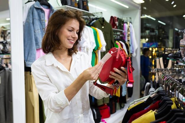 Lächelnde verheiratete frau in einem weißen klassischen hemd betrachtet den preis einer roten handtasche in einem speicher
