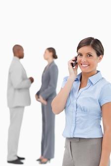 Lächelnde verkäuferin am telefon mit mitarbeitern hinter ihr