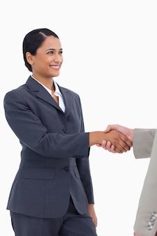 Lächelnde verkäuferin, die hand rüttelt