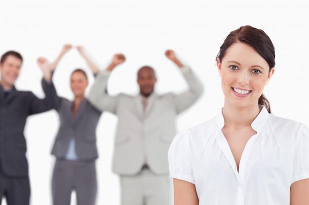 Lächelnde verkäuferin mit zujubelnden mitarbeitern hinter ihr