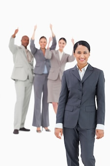 Lächelnde verkäuferin mit zujubelnden team hinter ihr