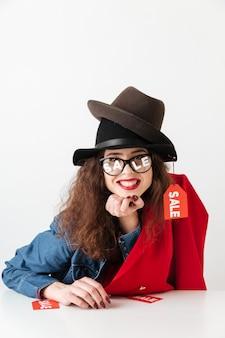 Lächelnde verkaufseinkaufsfrau, die verkaufsschilder trägt