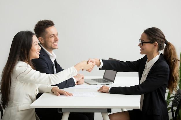 Lächelnde verschiedene geschäftsfrauen rütteln hände bei der gruppensitzung, abkommenkonzept