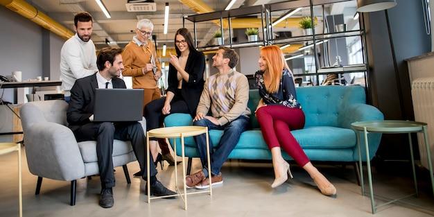 Lächelnde verschiedene geschäftsleute, die in einem büro sprechen