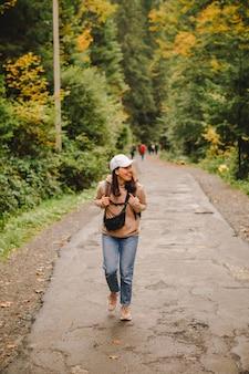 Lächelnde wandererfrau, die durch den herbstwaldweg-kopienraum geht