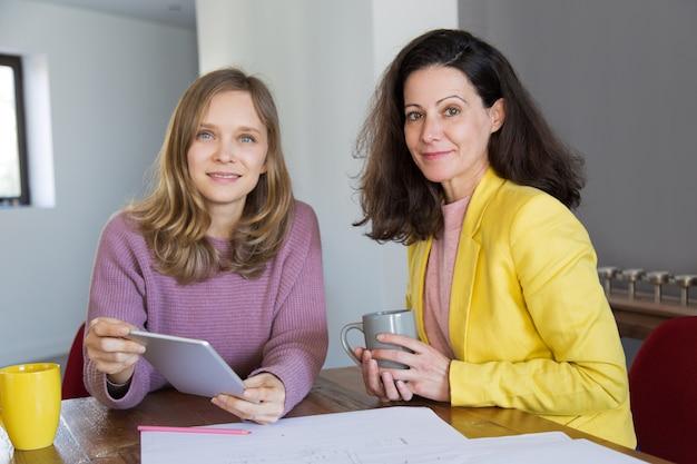 Lächelnde weibliche architekten, die tee trinken und tablette verwenden