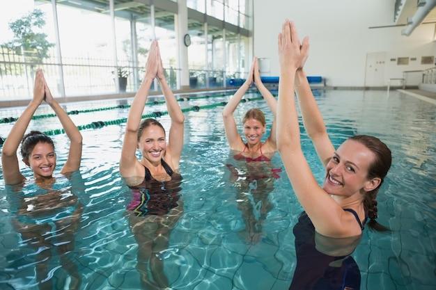 Lächelnde weibliche eignungsklasse, die aqua aerobic tut