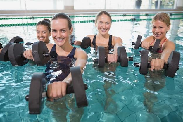 Lächelnde weibliche eignungsklasse, die aqua aerobics mit schaumdummköpfen tut