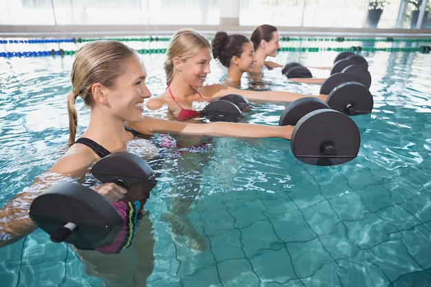 Lächelnde weibliche eignungsklasse, die aquaaerobic mit schaumdummköpfen tut