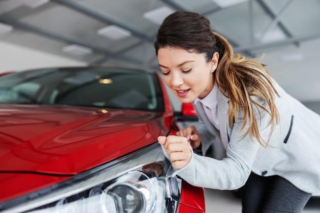 Lächelnde weibliche verkäuferin im anzug, die auto mit ihrem ärmel abwischt, während sie im exklusiven autosalon steht.