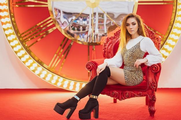 Lächelnde weihnachtsstimmung der schönheit, die auf einem roten stuhl sitzt