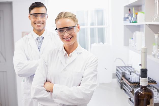Lächelnde wissenschaftler, welche die kameraarme betrachten, kreuzten