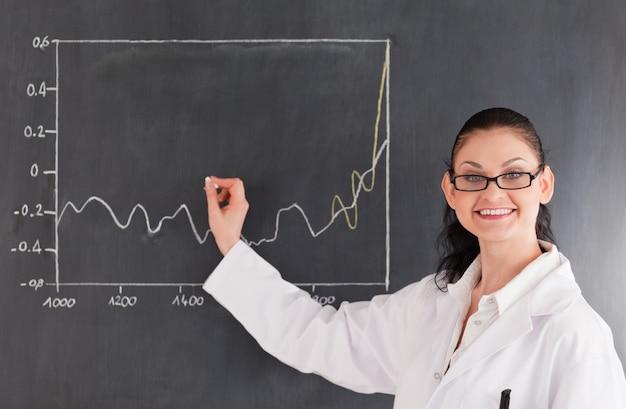 Lächelnde wissenschaftlerzeichnungsdiagramme auf der tafel