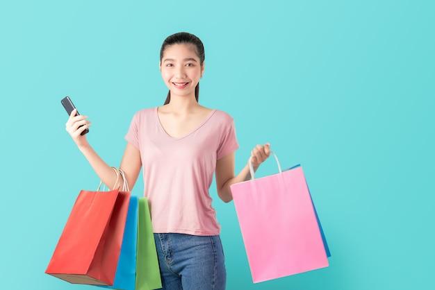 Lächelnde zufällige art der asiatischen frau, die smartphone und einkaufstaschen hält.