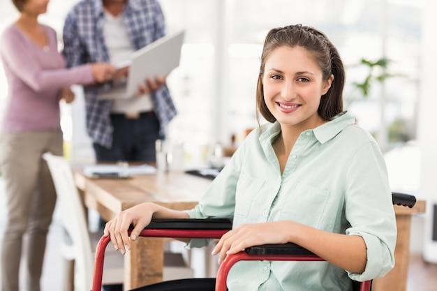 Lächelnde zufällige geschäftsfrau im rollstuhl