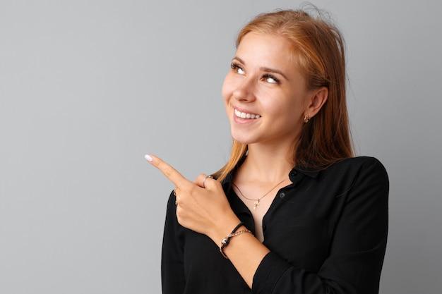 Lächelnde zufällige junge frau, die finger auf kopienraum zeigt