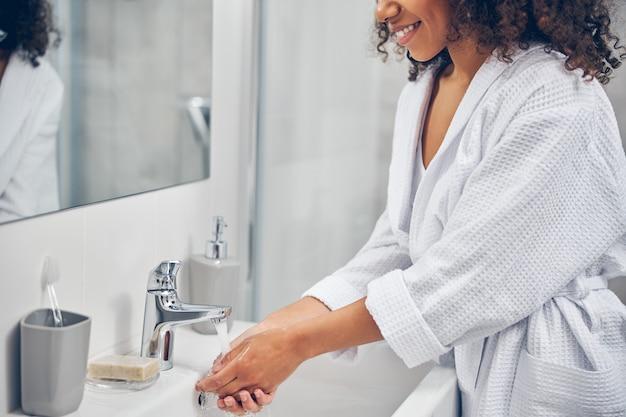 Lächelnde zufriedene frau in einem bademantel, die ein handwaschverfahren durchführt