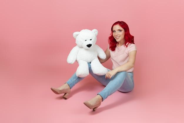 Lächelnde, zufriedene frau in jeans mit roten haaren und einem großen weißen teddybär, der auf dem boden sitzt