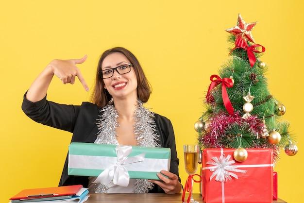Lächelnde zufriedene geschäftsdame im anzug mit brille, die ihr geschenk zeigt und an einem tisch mit einem weihnachtsbaum darauf im büro sitzt