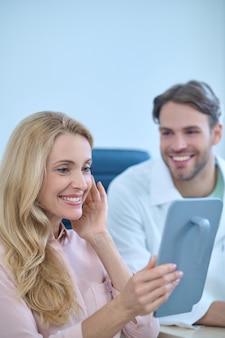 Lächelnde zufriedene patientin, die ein handglas vor ihrem gesicht hält
