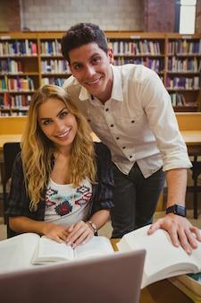 Lächelnde zusammenarbeitende studenten beim in der bibliothek bei tisch sitzen