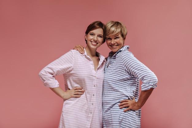 Lächelnde zwei damen mit moderner kurzer frisur in gestreiften sommerkleidern, die sich umarmen, lächeln und in die kamera auf isoliertem hintergrund schauen.
