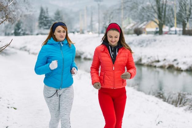 Lächelnde zwei freundinnen, die in der wintersaison rütteln