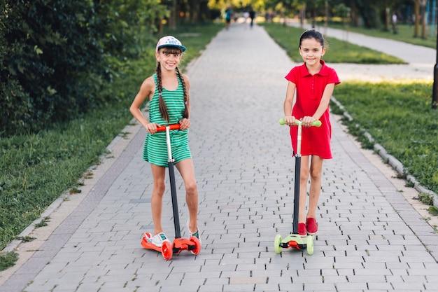 Lächelnde zwei mädchen, die auf stoßroller auf gehweg im park stehen