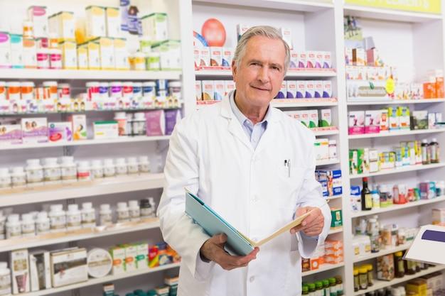 Lächelnder älterer apotheker, der notizbücher hält