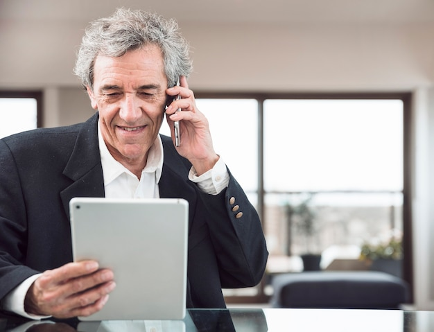 Lächelnder älterer mann, der am handy betrachtet digitale tablette auf arbeitsplatz spricht