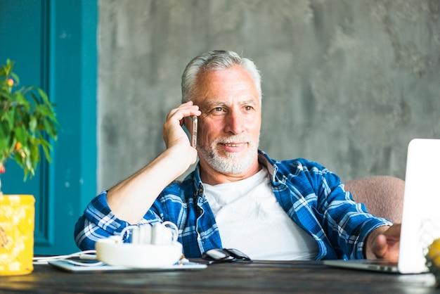 Lächelnder älterer mann, der am handy unter verwendung des laptops spricht