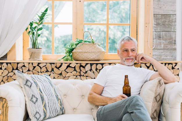 Lächelnder älterer mann, der auf dem sofa hält flasche bier sitzt