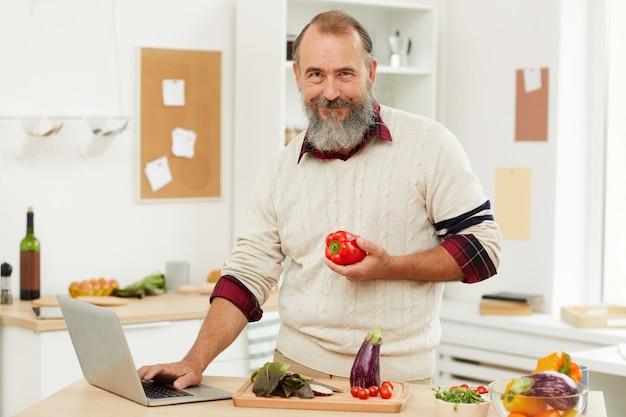 Lächelnder älterer mann, der durch online-tutorial kocht