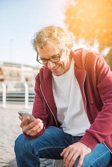 Lächelnder älterer mann, der im park betrachtet smartphone sitzt