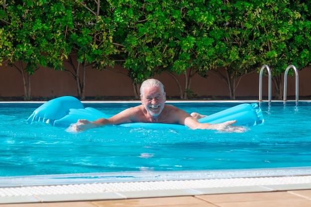 Lächelnder älterer mann, der im schwimmbad auf aufblasbarer matratze schwimmt und lachend in die kamera schaut. rentner genießt sommerferien