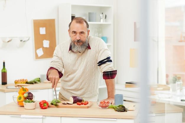 Lächelnder älterer mann, der in der küche aufwirft
