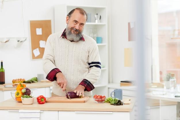 Lächelnder älterer mann, der in der küche kocht
