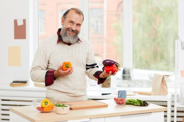 Lächelnder älterer mann, der kocht