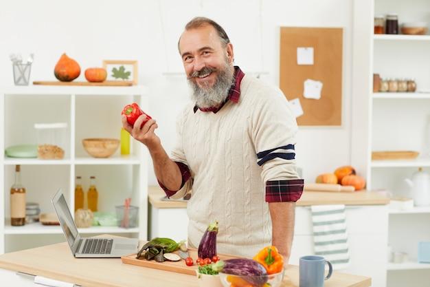 Lächelnder älterer mann, der mit paprika aufwirft