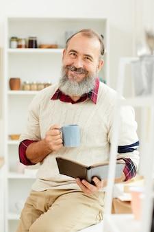 Lächelnder älterer mann, der morgenkaffee genießt