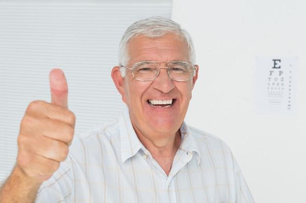 Lächelnder älterer mann, der oben daumen mit sehtafel im hintergrund gestikuliert