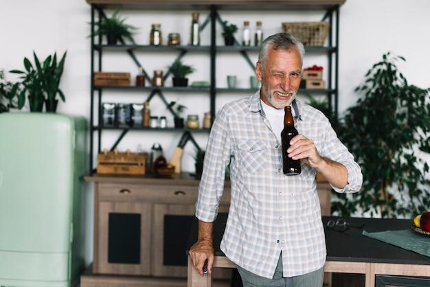 Lächelnder älterer mann, der sein auge blinzelt, bierflasche in der hand halten