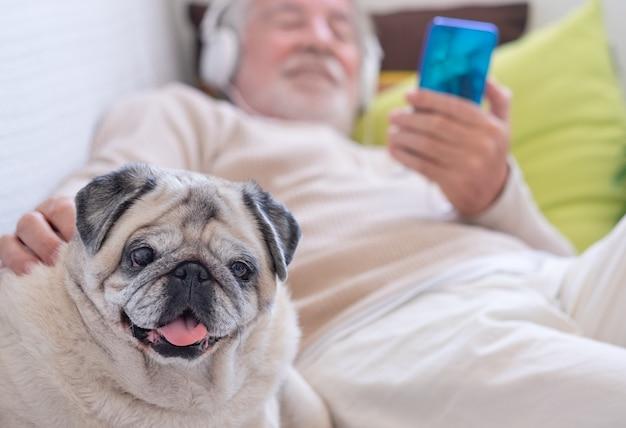 Lächelnder älterer mann, der sich mit seinem besten freund, einem reinrassigen mops, zusammen auf der couch zu hause hinlegt